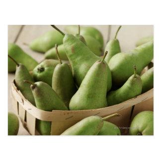 Peras verdes en cestito y tabla de madera postal