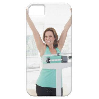 Pérdida de peso acertada. Pesaje feliz de la mujer iPhone 5 Protectores