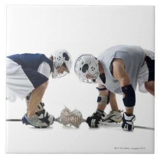 Perfil de dos hombres jovenes que juegan a lacross azulejo cuadrado grande