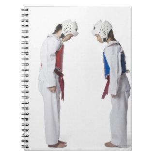 Perfil lateral de arquear de dos jugadores del Tae Cuaderno