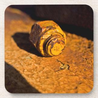 Perno y nuez oxidados posavasos de bebida