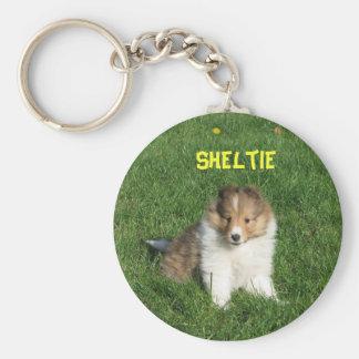 Perrito bonito del sheltie que se sienta en llavero redondo tipo pin