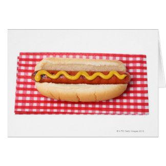 Perrito caliente en la mesa de picnic a cuadros felicitación