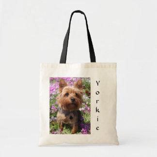 Perrito de Yorkie en las bolsas de asas del jardín