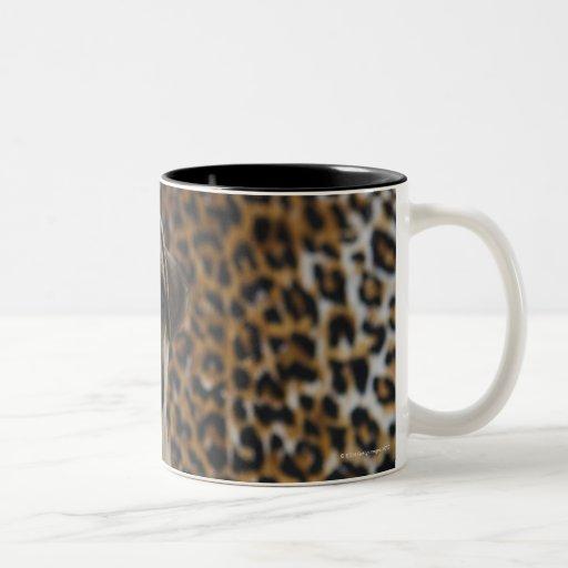 Perrito del barro amasado que se sienta contra el taza de café de dos colores