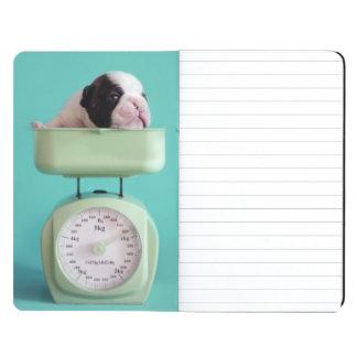 Perrito del dogo francés que comprueba el peso cuadernos grapados