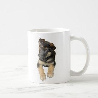 Perrito del pastor alemán y el decir en una taza