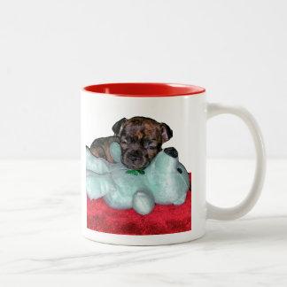 Perrito minúsculo con la taza del peluche