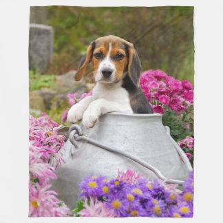 Perrito tricolor lindo del perro del beagle en la manta polar