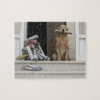 Perro del golden retriever que se sienta en la pue puzzles con fotos