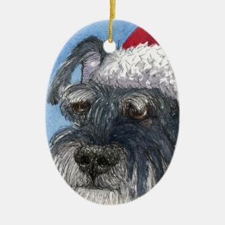 Perro del Schnauzer que lleva el gorra de Santa Adorno De Reyes