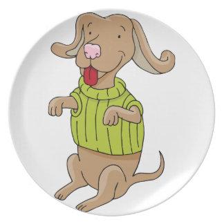 Perro del suéter que se sienta encima de dibujo platos para fiestas