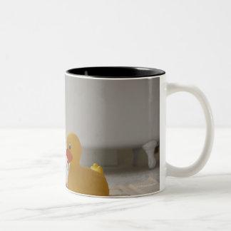 Perro en la estera con el pato plástico taza de café de dos colores