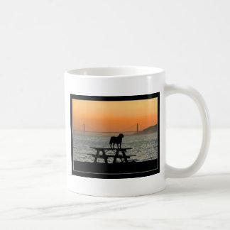 Perro en taza de la puesta del sol