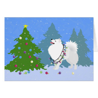 Perro esquimal americano que adorna el árbol de tarjeta de felicitación