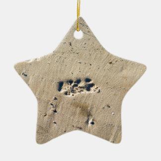 Perro grande de las huellas profundas en la orilla adorno navideño de cerámica en forma de estrella