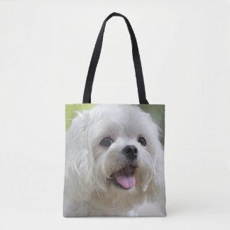 Perro maltés blanco que pega hacia fuera la lengua bolsa de tela