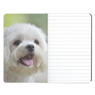 Perro maltés blanco que pega hacia fuera la lengua cuadernos