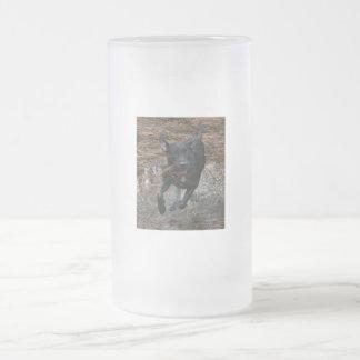 Perro negro del laboratorio con el funcionamiento taza de cristal
