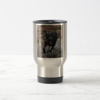 Perro negro del laboratorio con el funcionamiento taza de viaje