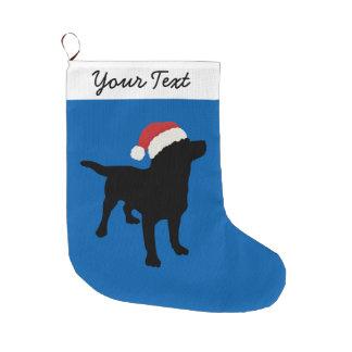 Perro negro del laboratorio con el gorra de Santa Calcetín Navideño Grande