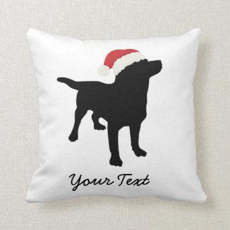 Perro negro del laboratorio con el gorra de Santa Cojín