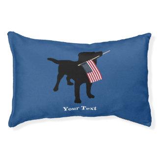Perro negro del laboratorio con la bandera cama para perro pequeño