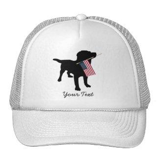Perro negro del laboratorio con la bandera gorros