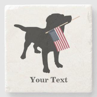 Perro negro del laboratorio con la bandera posavasos de piedra