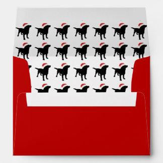 Perro negro del laboratorio del navidad que lleva sobre