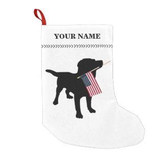 Perro negro del laboratorio que lleva a cabo calcetín de navidad pequeño