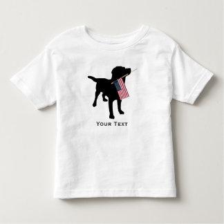 Perro negro del laboratorio que sostiene la playera de niño