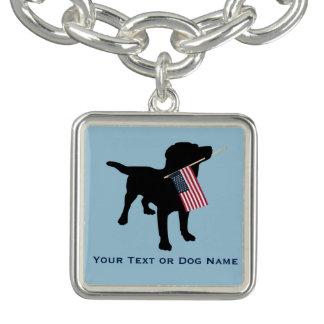 Perro negro del laboratorio que sostiene la pulsera con dije
