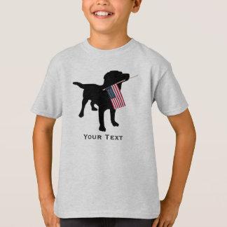 Perro negro lindo del laboratorio que sostiene la playera