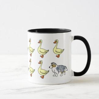 Perro pastor de Shetland que reúne la taza de los
