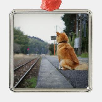 Perro que se sienta en la estación de tren adorno navideño cuadrado de metal