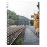 Perro que se sienta en la estación de tren libros de apuntes