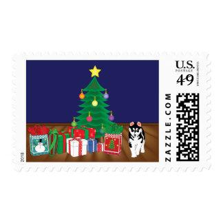 Perros esquimales que juegan por debajo la tarjeta timbres postales