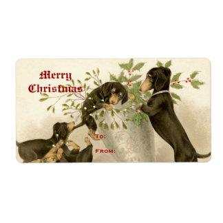 Perros que juegan con el muérdago del navidad y la etiqueta de envío
