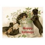 Perros que juegan con el muérdago del navidad y la postales
