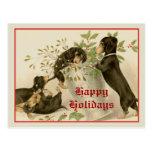 Perros que juegan con el muérdago del navidad y la tarjeta postal