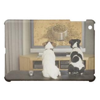 Perros que miran el plato del perro con la comida
