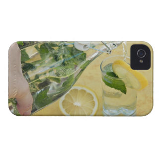 Person pouring water (mint-filled) into a glass iPhone 4 cover