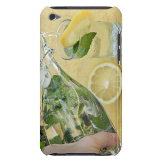 Person pouring water (mint-filled) into a glass iPod touch case