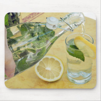 Person pouring water (mint-filled) into a glass mouse pad