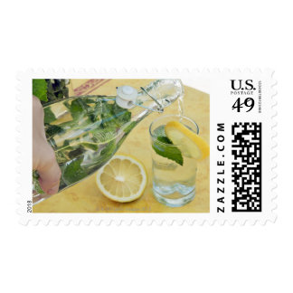 Person pouring water (mint-filled) into a glass postage