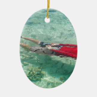 Person snorkeling in clear water Double-Sided oval ceramic christmas ornament