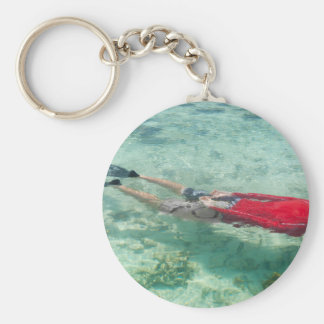 Person snorkeling in clear water key chains