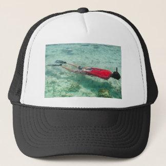 Person snorkeling in clear water trucker hat