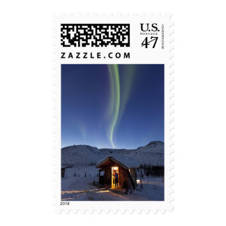 Person stands in doorway of Caribou Bluff cabin Postage